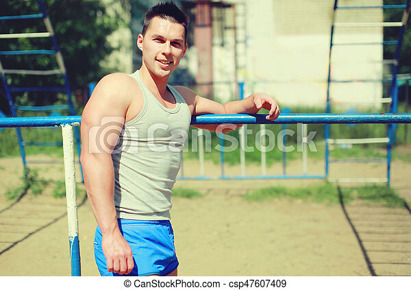 Sport, street workout concept - smiling sportsman near the horizontal bar outdoors