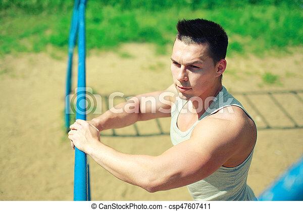 Sport, street workout concept - sportsman near the horizontal bar outdoors.