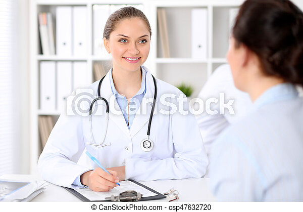 Friendly smiling doctor and patient sitting at the table. Very good news and high level medical service concept
