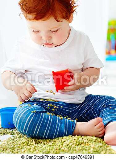 cute redhead baby boy developing fine motility skills by playing with green peas at home