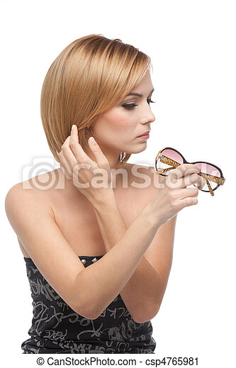 a portrait of a young, blonde woman, looking at her reflexion in a pair of sun glasses she holds in one hand and touching up her hair with the other hand. - csp4765981