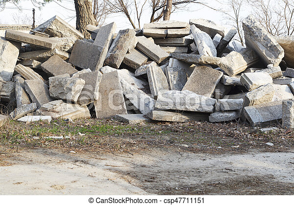 Big heap of the concrete gray plates scattered in the form of the mountain lying on the earth