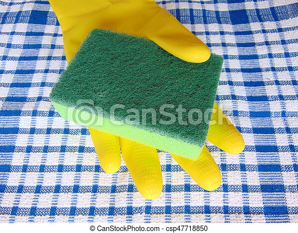 Hand in yellow rubber glove holding a cleaning brush on blue cloth