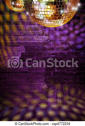 Golden mirror balls reflect lights on dramatic dark disco brick wall - csp4772234