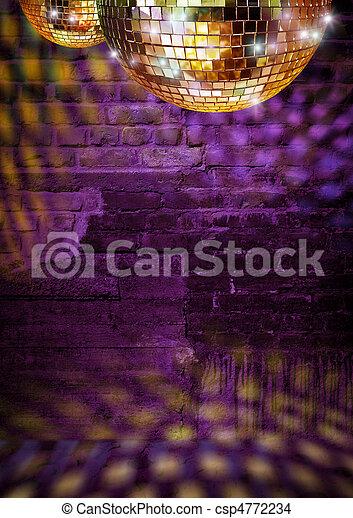Golden mirror balls reflect lights on dramatic dark disco brick wall - csp4772234