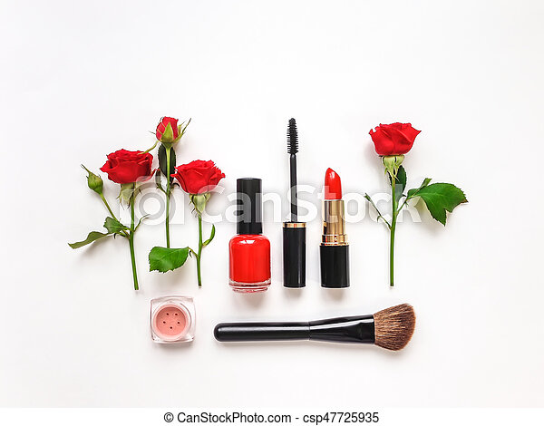 Decorative flat lay composition with woman cosmetics and red rose flowers. Flat lay, top view on white background, make up composition