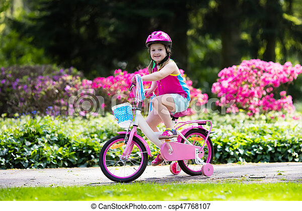 Child riding bike. Kid on bicycle in sunny park. Little girl enjoying bike ride on her way to school on warm summer day. Preschooler learning to balance on bicycle in safe helmet. Sport for kids.