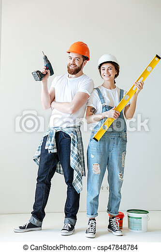 Full length portrait of a smiling happy couple wearing hardhats and holding tools over white