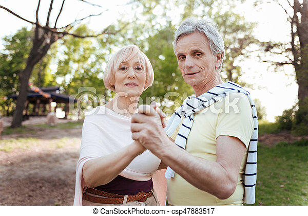 The power of love. Charming caring retired couple expressing love while enjoying weekend and dancing in the park