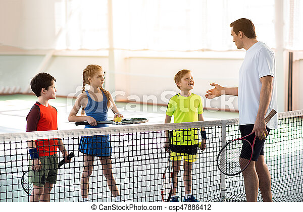 Confident male trainer is explaining how to play tennis to children. Boy is looking at him with aspiration and laughing