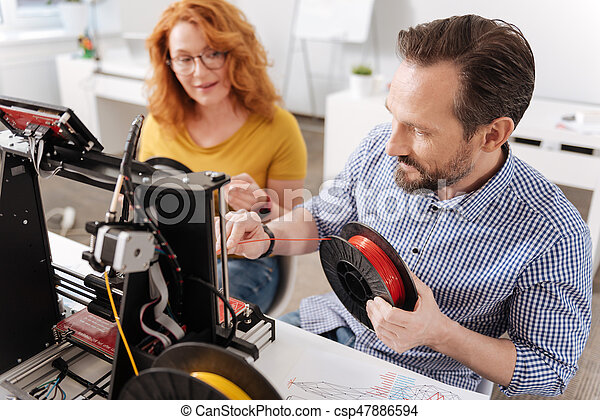 Printing materials. Professional positive male designer holding 3d filament and changing it in the 3d printer while working with new technologies