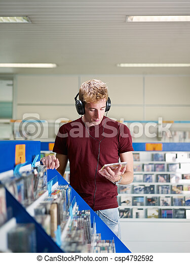 guy listening music in cd store - csp4792592