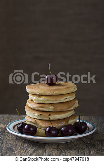 Stack of pancakes with berries on a brown wood table - csp47947618