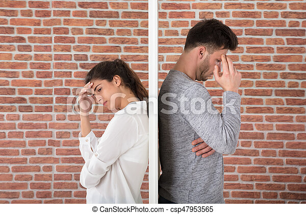 Depressed Contemplated Young Couple Against Brick Wall