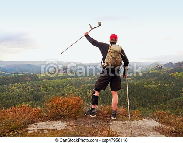 Wounded tourist with crutch above head achieved mountain peak. Hiker with backpack and knee brace feature. Deep valley bellow man with hand in air. Spring daybreak