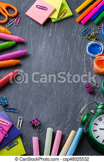 Back to school, children education concept. Assortment of supplies, crayons, pens, chalks, alarm clock on a black chalkboard. Copy space background, top view flat lay overhead