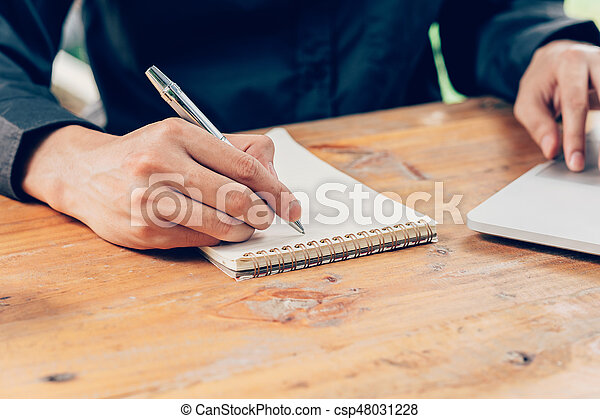 Man hand writing notebook paper and using laptop on wood table in coffee shop with vintage toned filter.