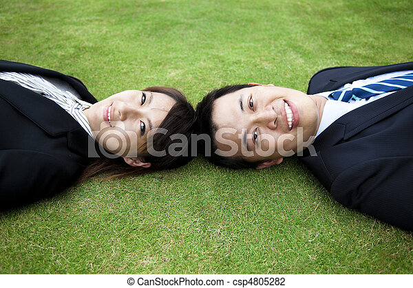 Attractive young adult couple and lay on the grass field - csp4805282