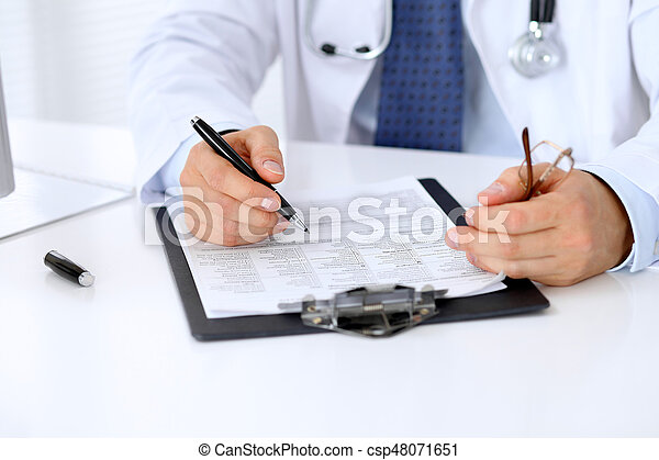 Close up of male doctor is sitting at the table and filling up medical history form.