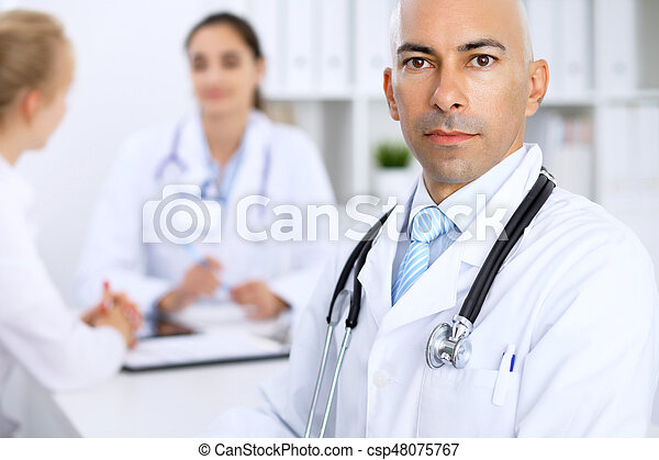 Confident bald doctor man with medical staff at the hospital.