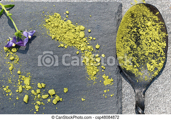 Green Matcha powder in a spoon on a slate colored tile - csp48084872