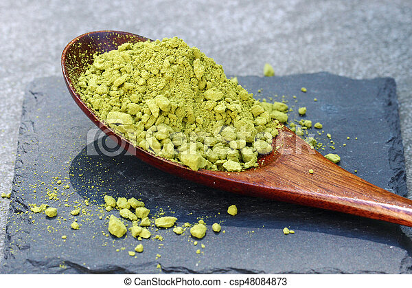 Green Matcha powder in a spoon on a slate colored tile - csp48084873