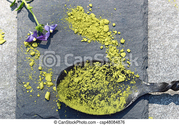Green Matcha powder in a spoon on a slate colored tile - csp48084876