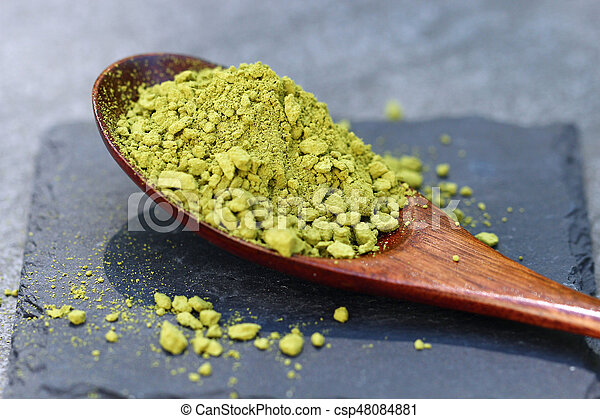 Green Matcha powder in a spoon on a slate colored tile - csp48084881