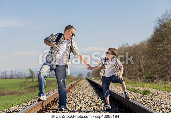 Father and son walking on the railway at the day time. People having fun outdoors. Concept of friendly family.