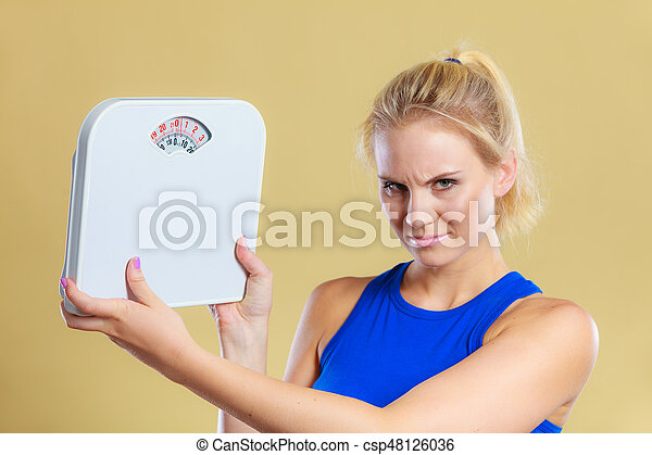 Fit fitness woman with scale. Frustrated angry blonde girl holding weight scales. Time for slimming weightloss, diet and healthy lifestyles concept