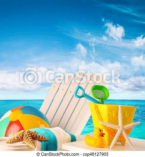 Beach toys on summer chair by the ocean - csp48127903