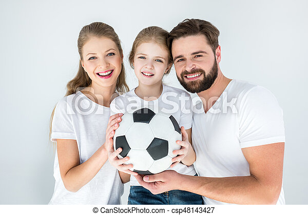portrait of happy parents and daughter holding soccer ball on white