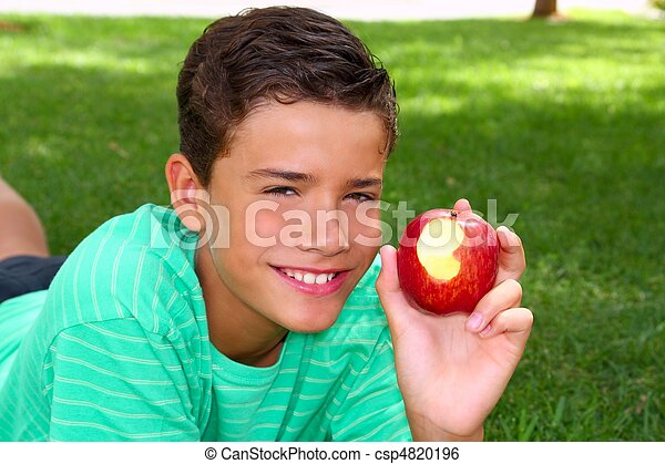 boy teenager eating red apple on garden grass - csp4820196