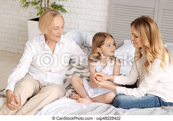 Love to a kid. Elegant senior lady and her smiling young daughter devoting all their attention to a cute little girl sitting in between them.