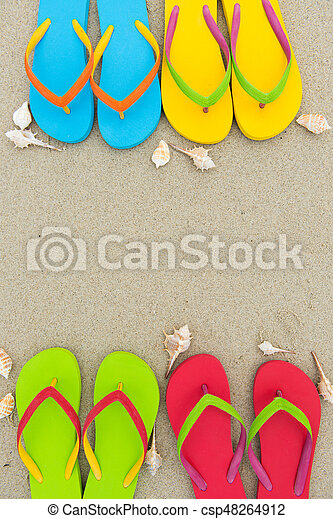 Colourful flip flops on sandy beach, with copy space