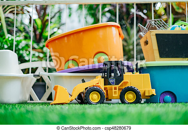 Tracktor toy car with toy boxes in the garden.