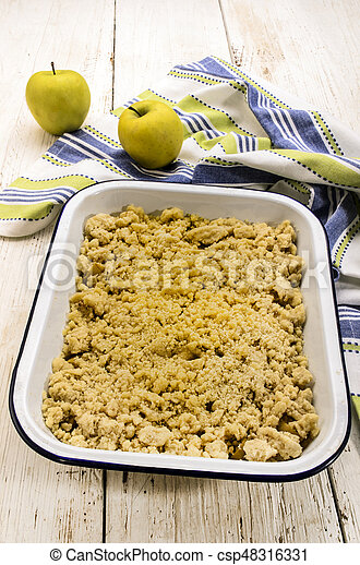 british apple crumble, freshly baked, in an white and blue enamel bowl