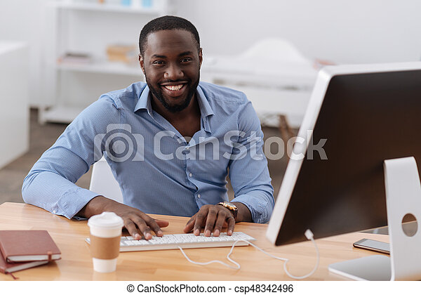 I like my job. Positive delighted joyful man sitting at the computer and smiling while enjoying his job