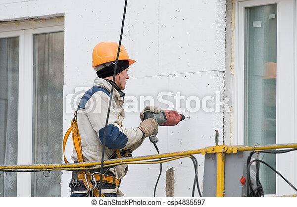 laborer in helmet at facade works - csp4835597