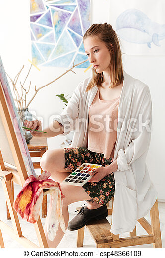 Photo of beautiful young caucasian lady painter at workspace. Looking aside.