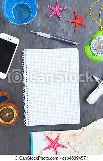 Travel concept - frame with compasses, strafish and phne, copy space on empty ruled notebook