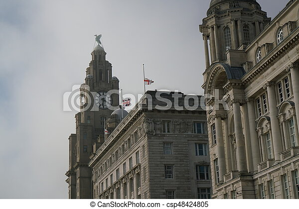 Liverpool,UK-May 24, 2017:The Union Jack and the flag of England at half-staff on a building at Liverpool waterfront. A terrorist attack caused 22 fatalities and dozens of injuries at a concert in Manchester