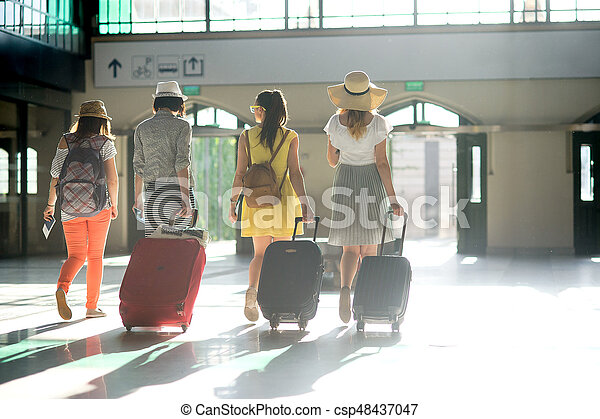Group of young tourists at the station. In hands at girls suitcases, tickets, passports. Summer tourism. View from a back.