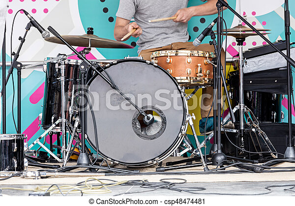 young musician playing drums on outdoor stage during the music festival