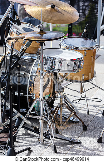 drum set with microphones standing on outdoor stage