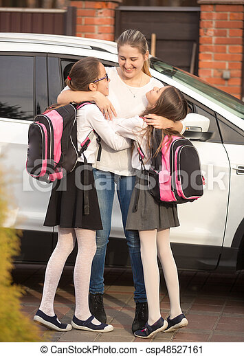 Happy mother meeting daughters near the car after school