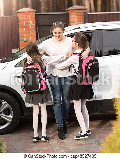 Two happy smiling girls running to mother meeting them after school