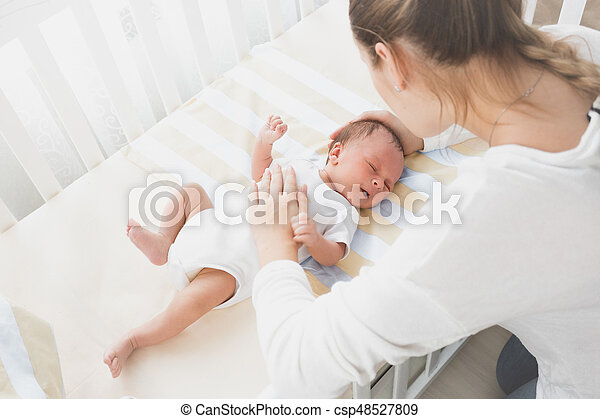 Mother sitting near the cradle and holding baby's hand - csp48527809