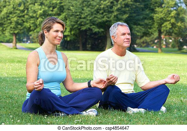 Happy elderly senior couple doing yoga