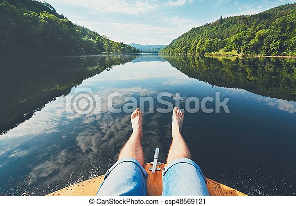 Summer relaxation on the river. The legs of a man sitting on the bow of the boat. Vltava river near Prague, Czech Republic
